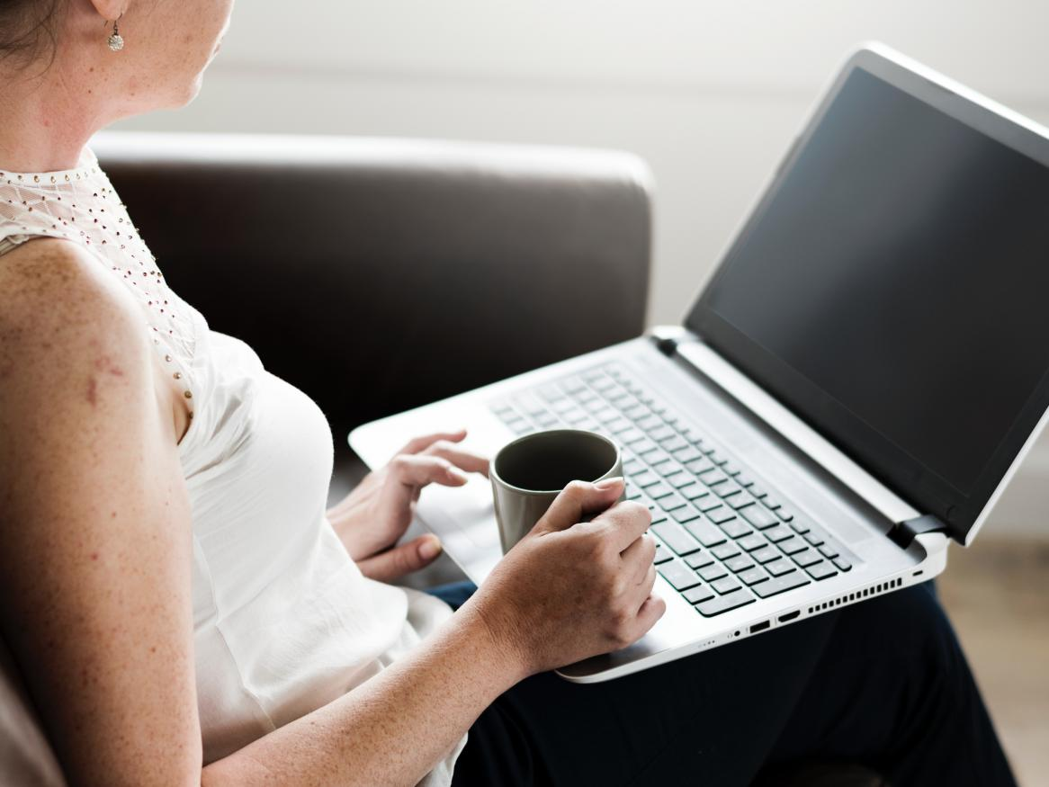 woman with coffee sitting on chair with laptop