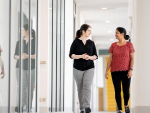 Female research study participant and female researcher walking down corridor, having conversation