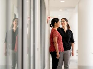 Female participant having height measured by female researcher in corridor