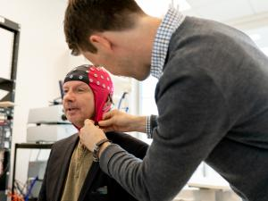 Male research study participant being fitted with skull cap by male researcher