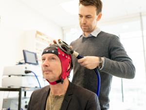 Male research study participant wearing skull cap undergoing assessment by male researcher