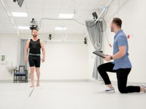 Male research study participant wearing CGI dots walking and being monitored in gait lab by researcher