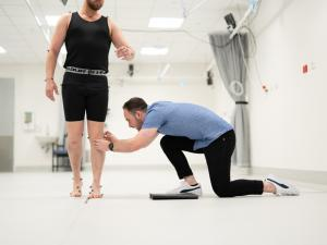 Male research study participant being fitted with CGI dots by researcher in gait lab