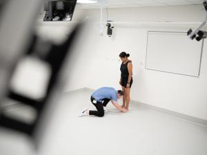 Female research study participant being fitted with CGI dots by researcher in gait lab