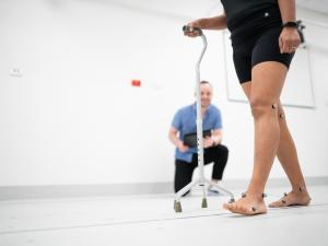 Research study participant wearing CGI dots and using mobility aid walking and being monitored in gait lab by researcher