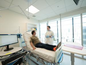 Male research study participant lying on bed in clinical room discussing procedure with researcher