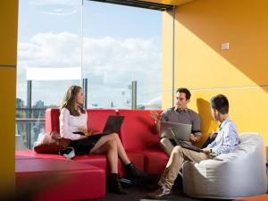 Three students sitting on couches in student space at the Adelaide Health and Medical Sciences building