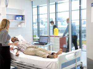 Clinical room with research study participant lying in a bed being monitored by a researcher
