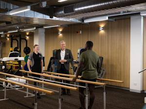 Image of people taking next to parallel bars in rehab gym