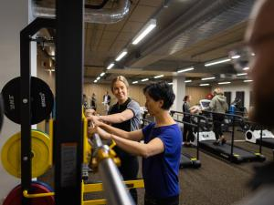 Image of physio student helping lady at a bar in the rehab gym
