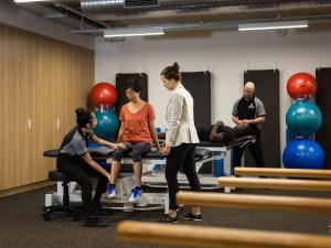 Image of physio student examining patient in rehab gym