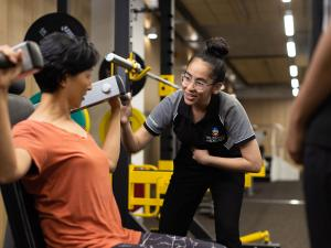 Image of physio student helping patient with weights in rehab gym