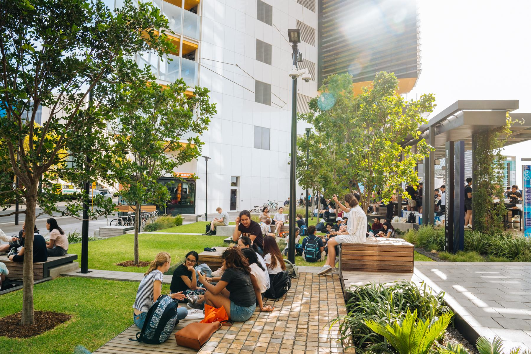 Students sitting and chatting in the Urban Park, outside the AHMS building