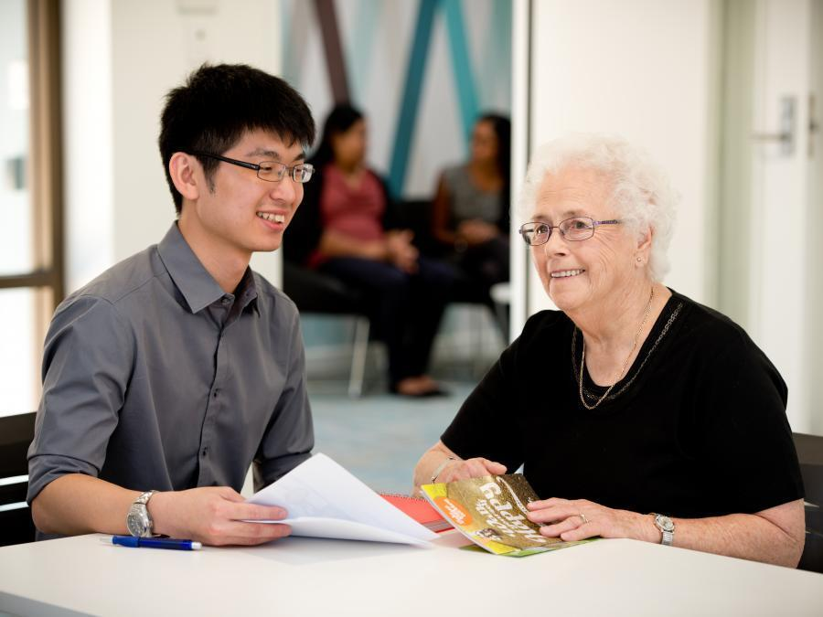 Young man sitting at a desk with elderly woman, discussing paperwork