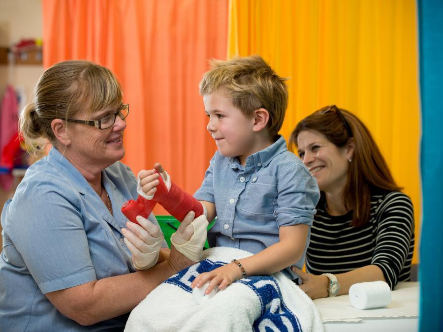 Child sitting up in hospital bed with red plaster cast on arm, smiling at mum and nurse