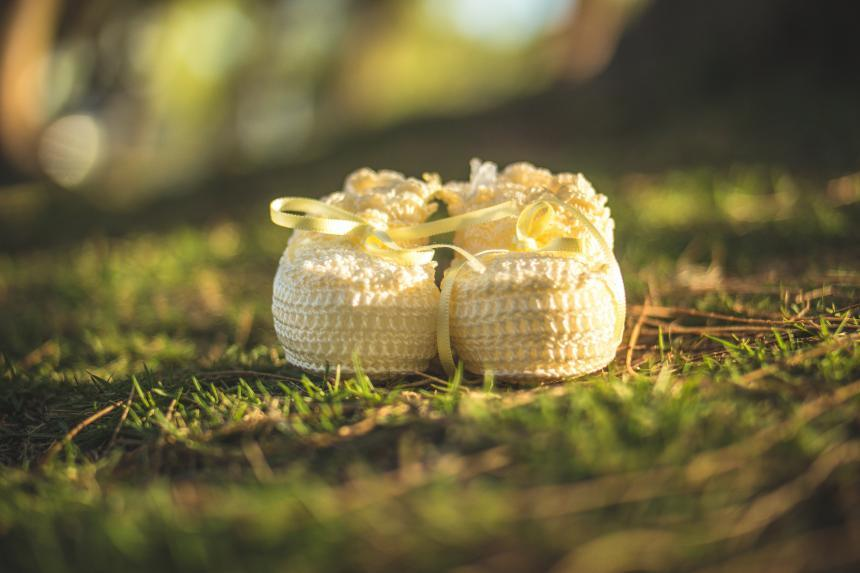 A pair of yellow baby booties placed on grass