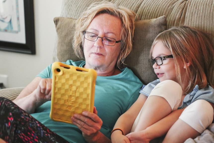 Grandmother and granddaughter sitting on couch playing hand-held game