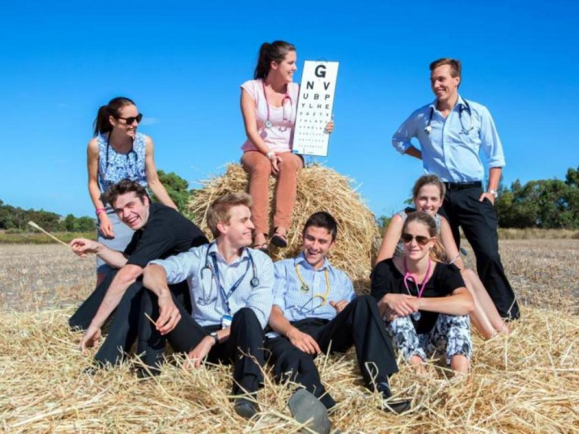 Eight students sitting on hay bale, smiling, one student holding up with eye chart