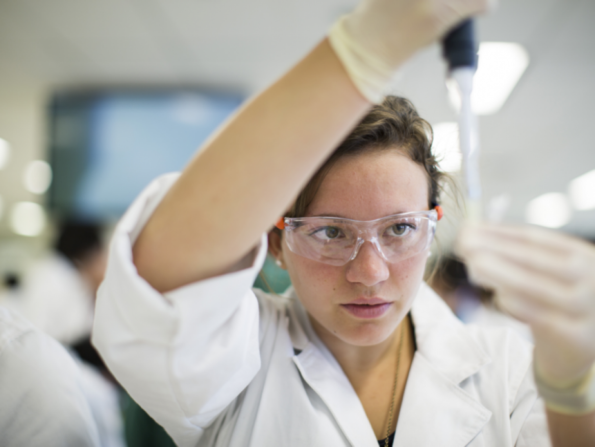 Researcher in lab coat and safety glasses using laboratory apparatus