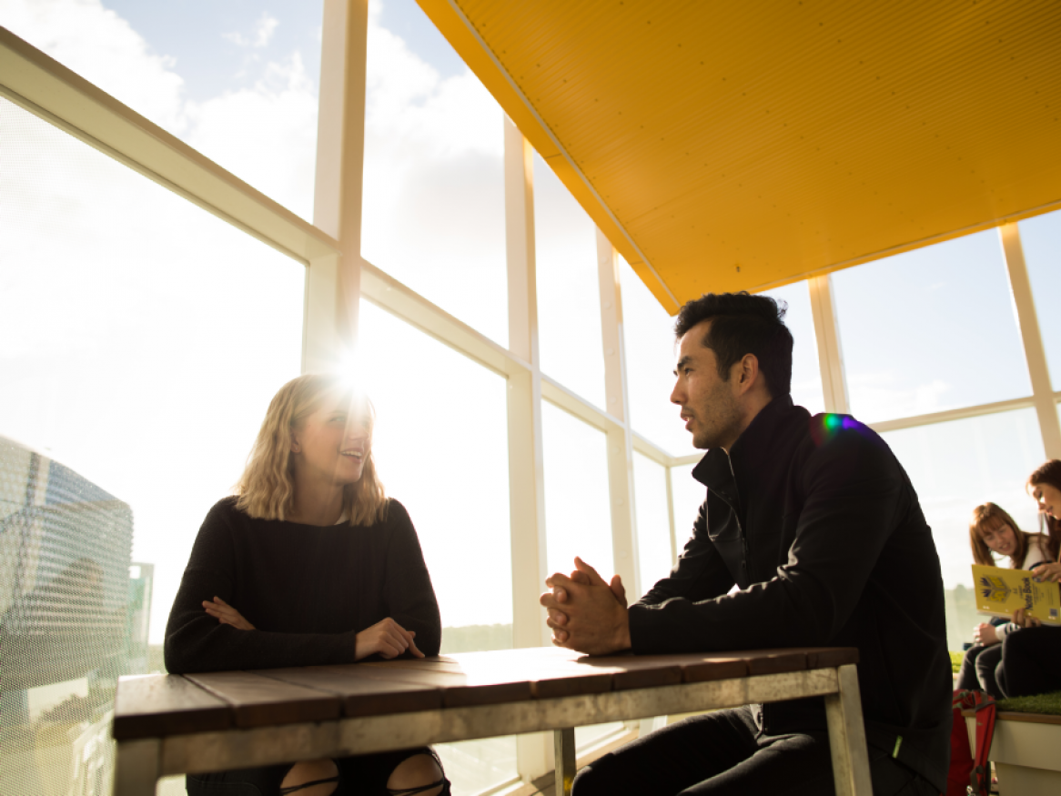 Two students sitting at a table inside the AHMS building talking, with sun flare through windows behind them