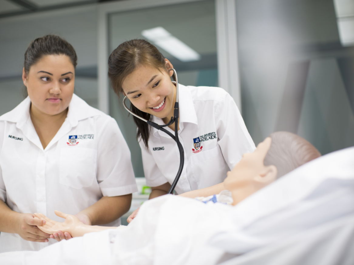Two nursing students assessing simulated patient